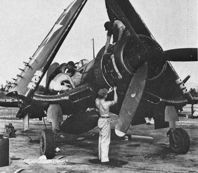 To repair battle damage, a F4U-1D in a service area in the Gilbert Islands, July 12, 1945.